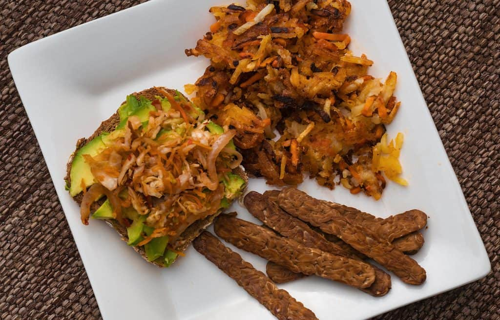 Plant-based vegan breakfast food: avocado toast with kimchi, bacon-flavored tempeh, and root vegetable hashbrowns.